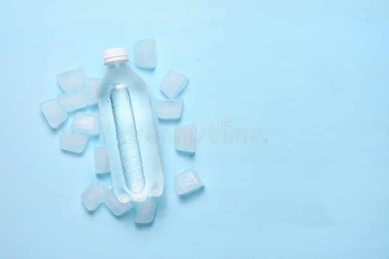水瓶和冰块在桌上与文本空间 免版税图库摄影