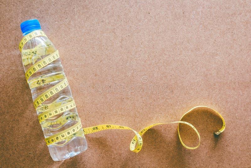 水瓶和卷尺在木背景 免版税库存图片