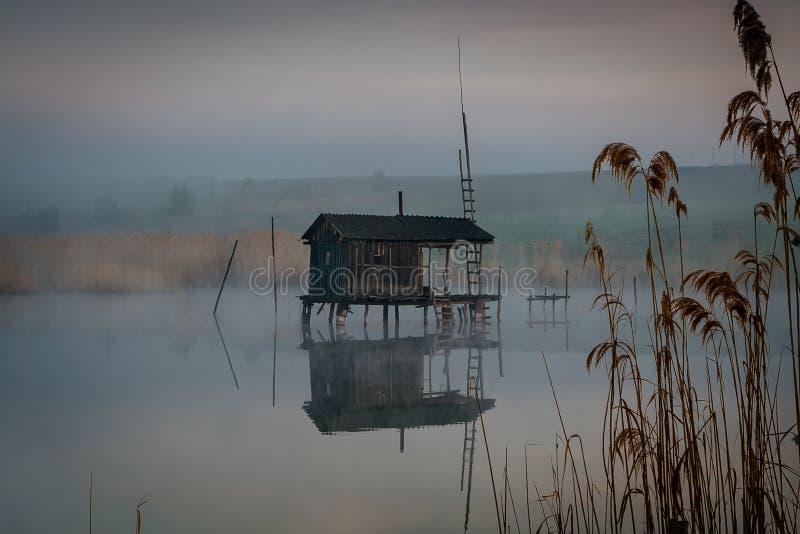 水的渔房子在早晨雾 库存照片