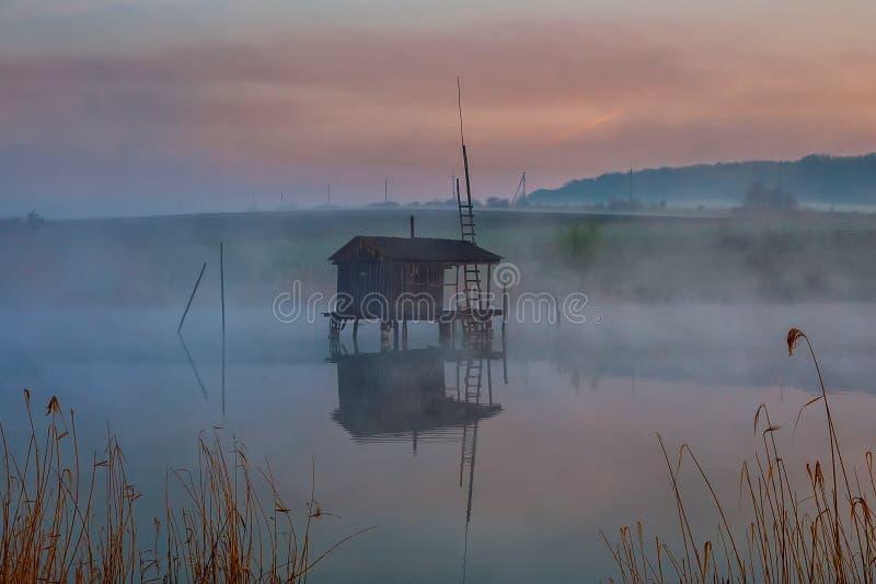水的渔房子在早晨雾 库存图片