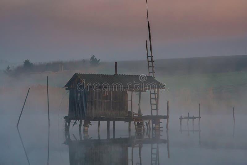 水的渔房子在早晨雾 免版税库存图片