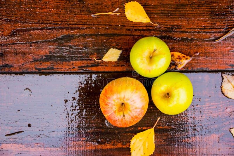 水盖的三个湿金黄绿色苹果滴下在棕色湿自然老木桌表面顶部 顶视图和 免版税库存图片