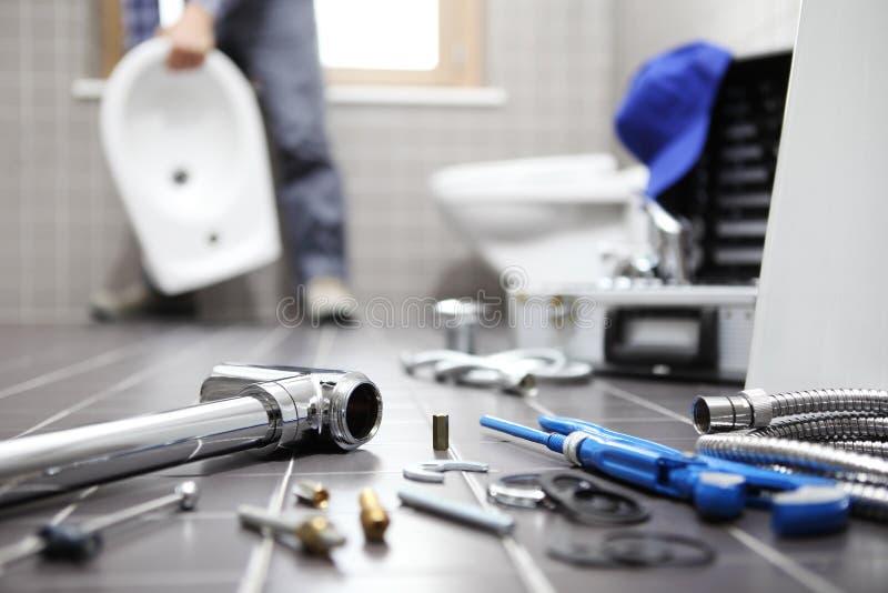 水管工在工作在卫生间,测量深度修理公司,聚集 免版税库存图片