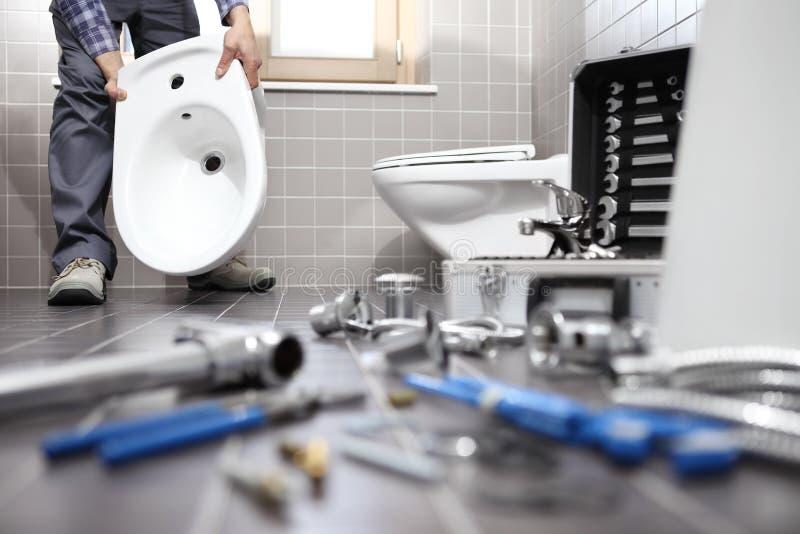 水管工在工作在卫生间,测量深度修理公司,聚集 免版税库存照片