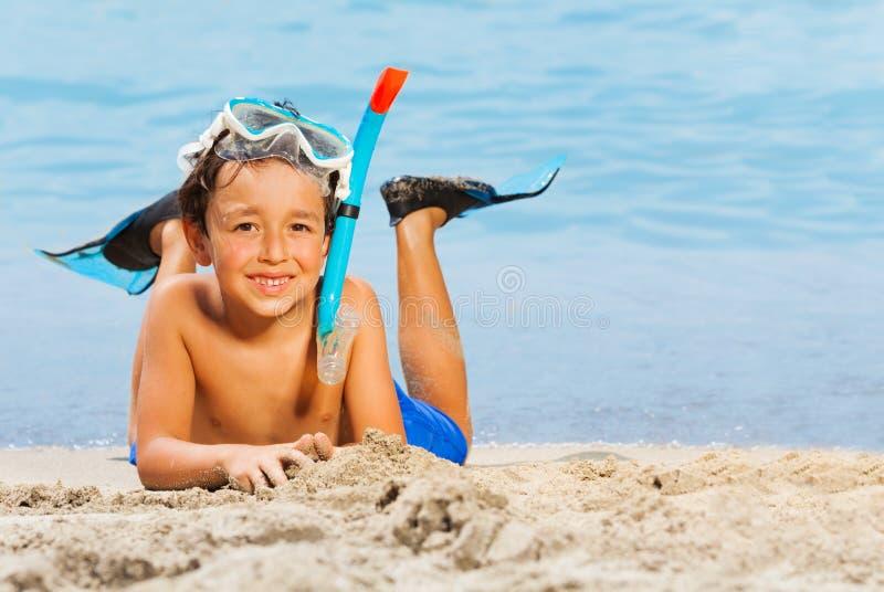 水肺面具的在海滩的小男孩和鸭脚板 免版税库存照片