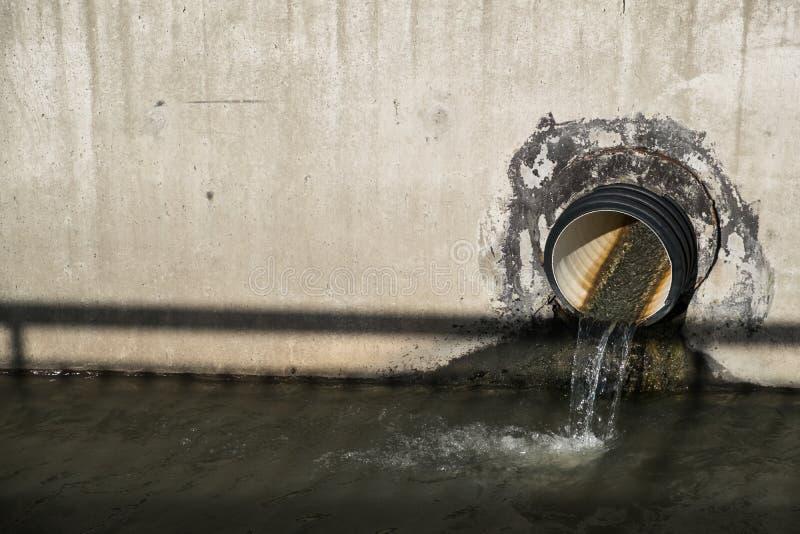 水通过管子被排泄入渠道 库存图片