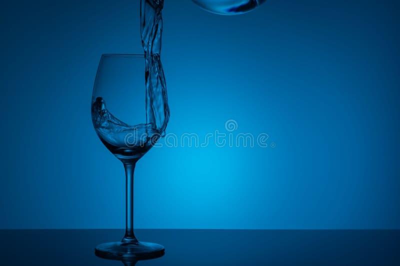 水飞溅在一块玻璃的在蓝色背景 库存照片