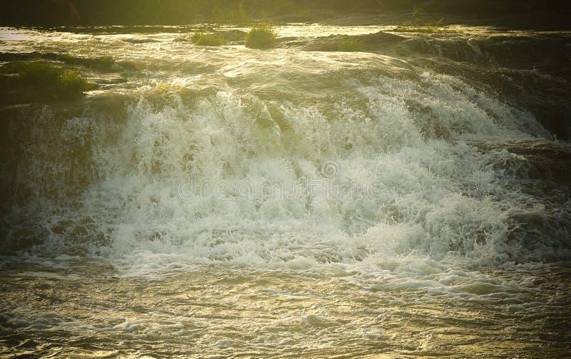 水-洪水强有力的流程与明亮的阳光的-自然水色背景 免版税库存照片