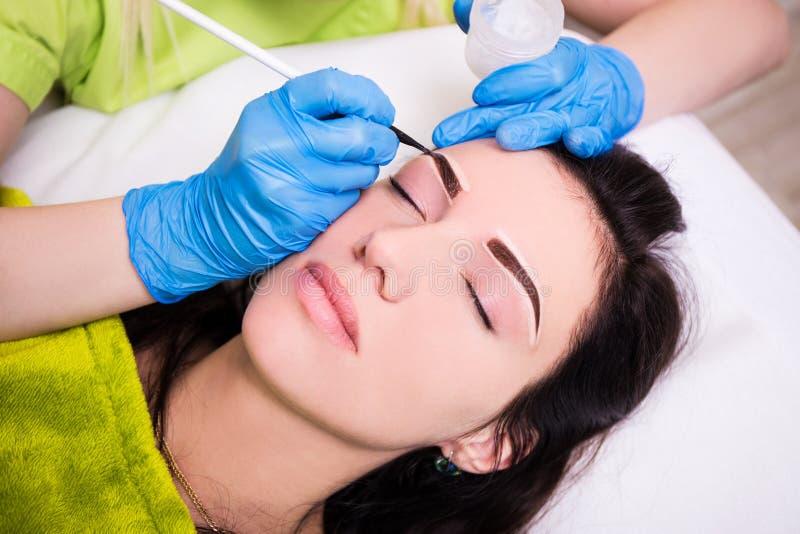 永久眼眉组成-申请麻醉和p的美容师 免版税库存图片