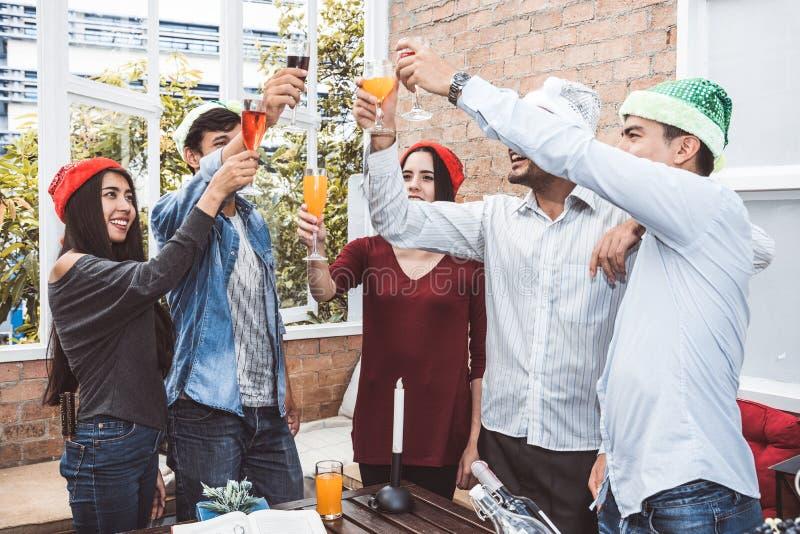 永远敬酒水杯的年轻人室外Xmas党射击在屋顶大阳台作为友谊 年轻朋友停留 免版税库存照片