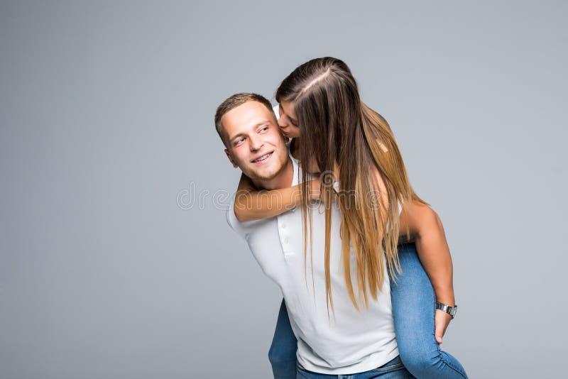 永远爱 年轻布鲁内特英俊的男朋友扛在肩上他逗人喜爱的恋人,佩带的便服,在灰色背景 图库摄影