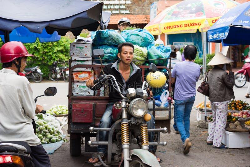 永隆,越南- 2014年11月30日:运输果子的摩托车司机在永隆市场,湄公河三角洲上 由马达的运输 免版税库存照片