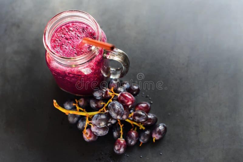 汁液圆滑的人葡萄玻璃瓶莓果饮食 免版税库存图片
