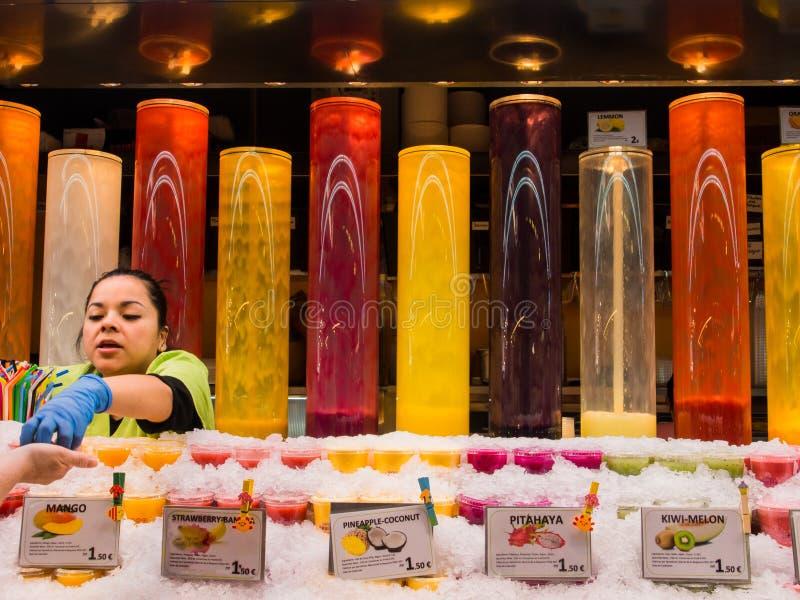 汁液客商在巴塞罗那市场上 库存照片