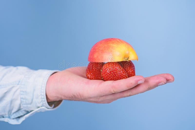 汁液成份 成熟果子莓果新有机收获  男性手用草莓和一半苹果蓝色 库存照片