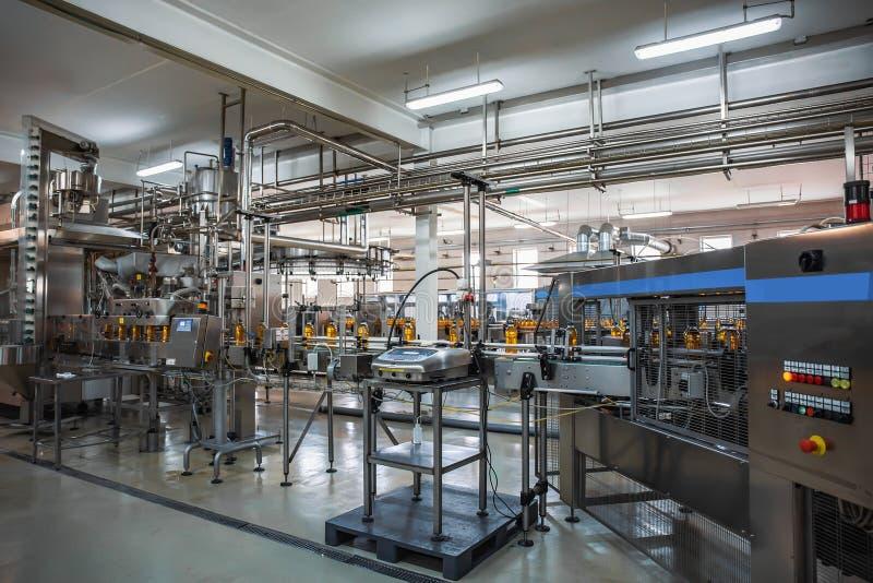 汁液生产线自动传送带在饮料植物或工厂,现代计算机化的工业设备的 库存图片