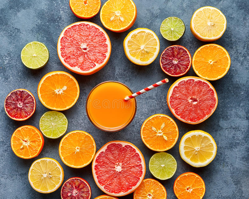 汁液用柑桔,葡萄柚,橙色在蓝色背景 顶视图,选择聚焦 戒毒所,节食,干净吃 免版税库存照片