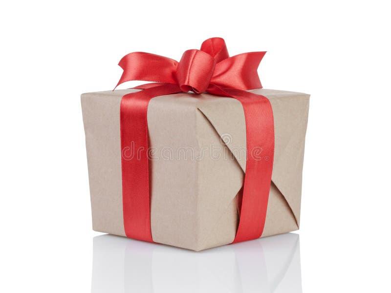 求礼物盒的立方包裹与牛皮纸和红色弓 库存图片