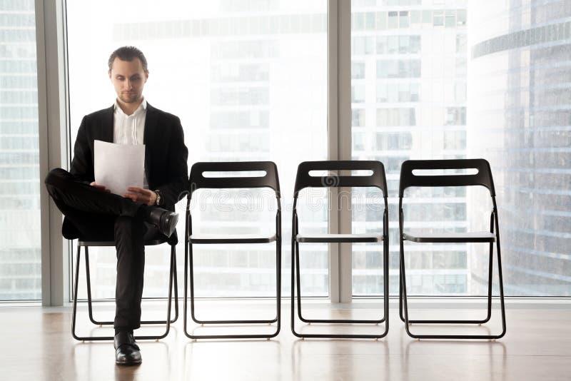 求职者读简历,当等待采访时 免版税库存照片