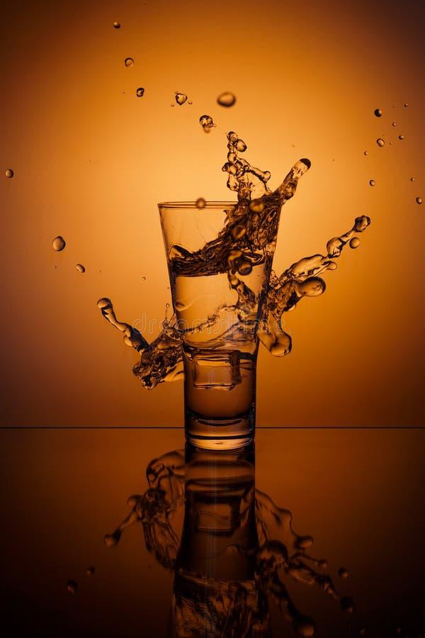 求飞溅水的玻璃冰的立方 库存照片