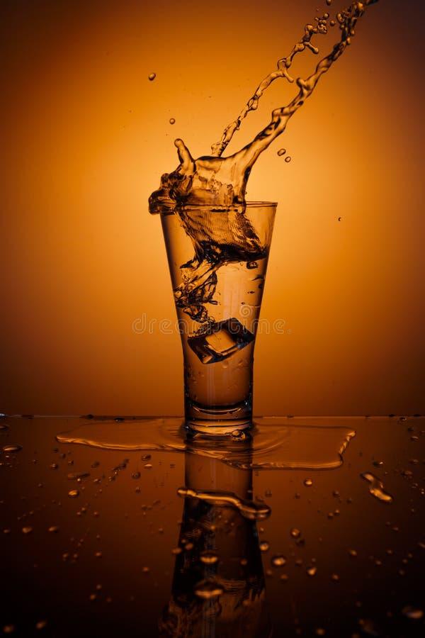 求飞溅水的玻璃冰的立方 免版税库存图片