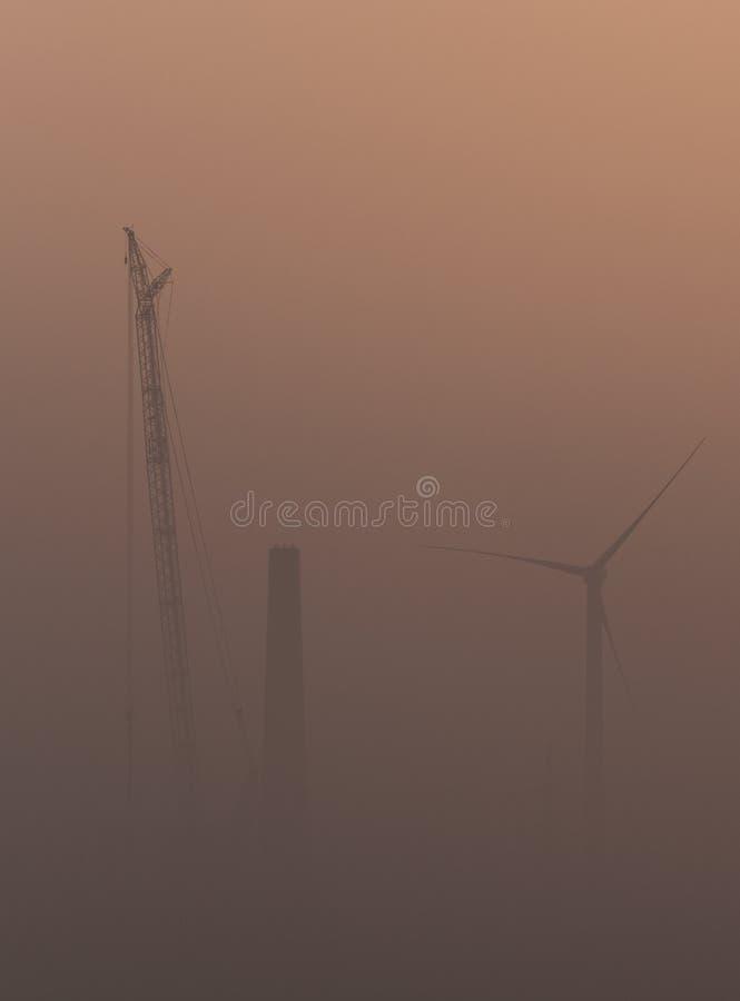 汇编的大起重机在温暖的雾的风轮机 免版税库存图片