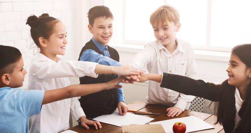 汇集他们的手的小学生户内 免版税库存照片