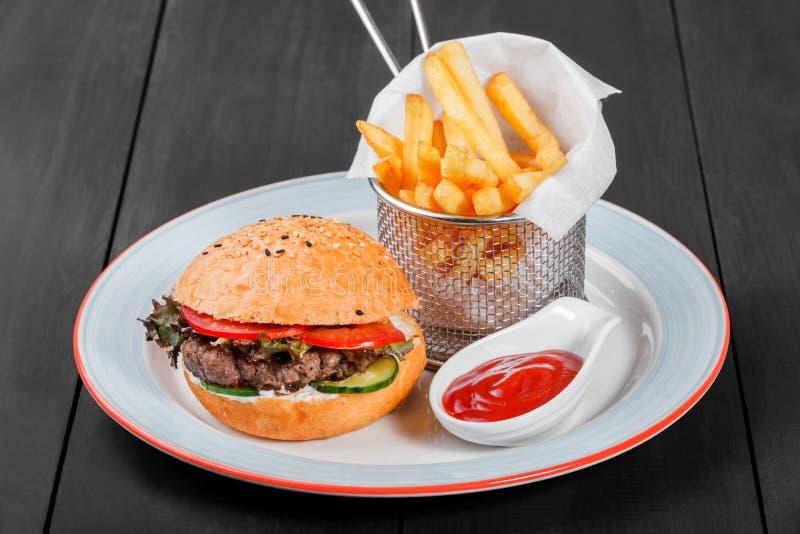 汉堡、汉堡包用炸薯条,番茄酱、蛋黄酱、新鲜蔬菜和乳酪在板材在黑暗的木背景 库存图片