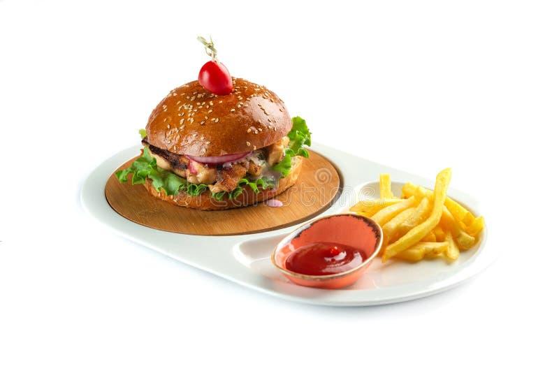 汉堡包、薯条和西红柿酱在白色背景隔绝的一块白色卵形板材 库存照片