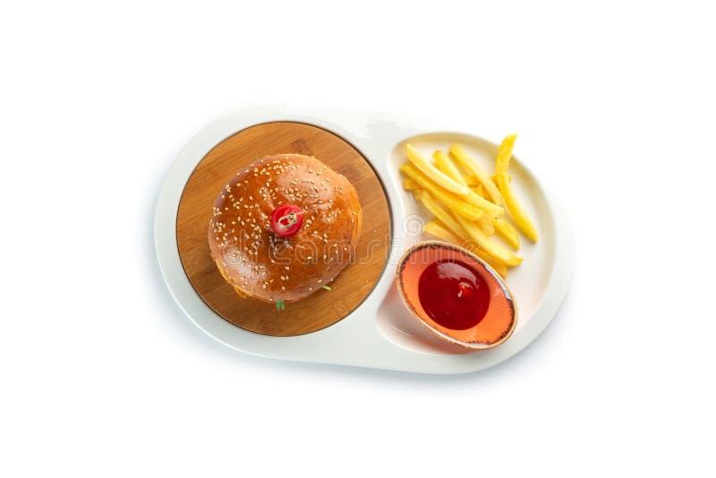 汉堡包、薯条和西红柿酱在白色背景隔绝的一块白色卵形板材 免版税库存图片