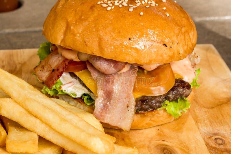 汉堡包和炸薯条在木头 库存图片