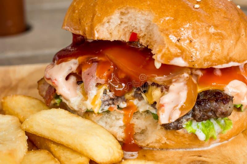 汉堡包和炸薯条在木头 免版税图库摄影
