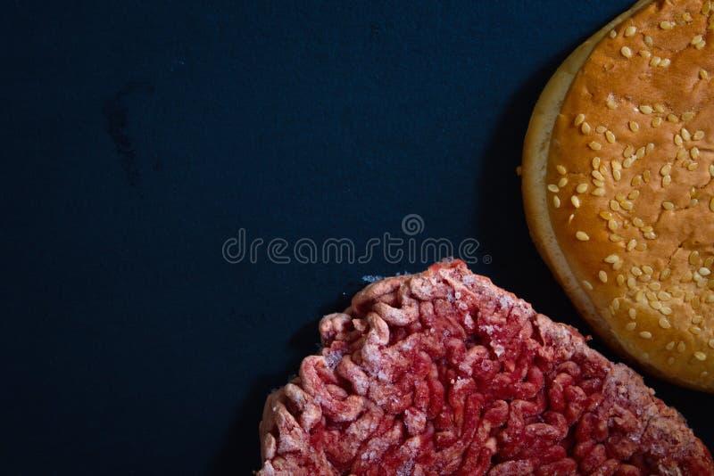 汉堡包小圆面包和结冰的未加工的牛肉或猪肉汉堡包 免版税图库摄影