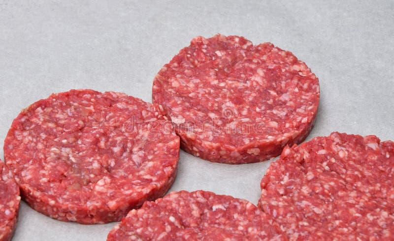 汉堡包的生肉汉堡在羊皮纸 库存照片
