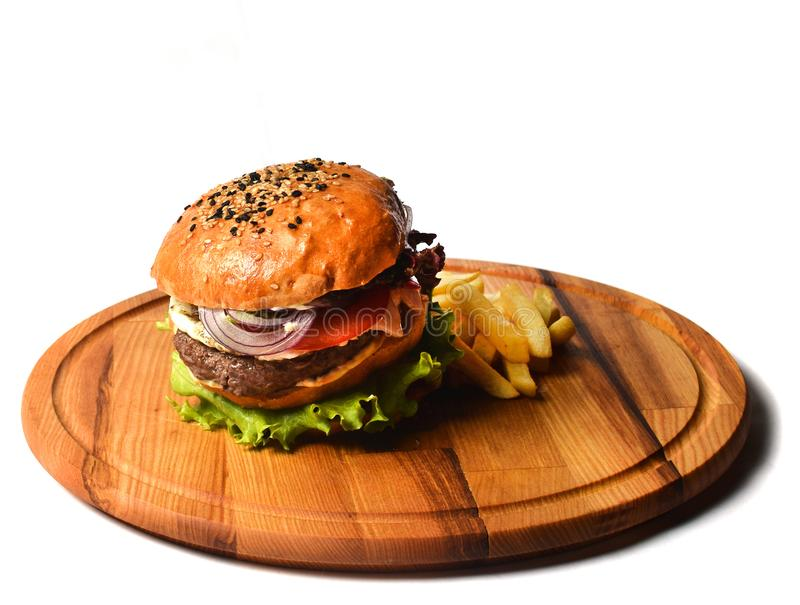 汉堡用在一个木板的炸薯条 在白色背景隔绝的快餐 免版税库存照片
