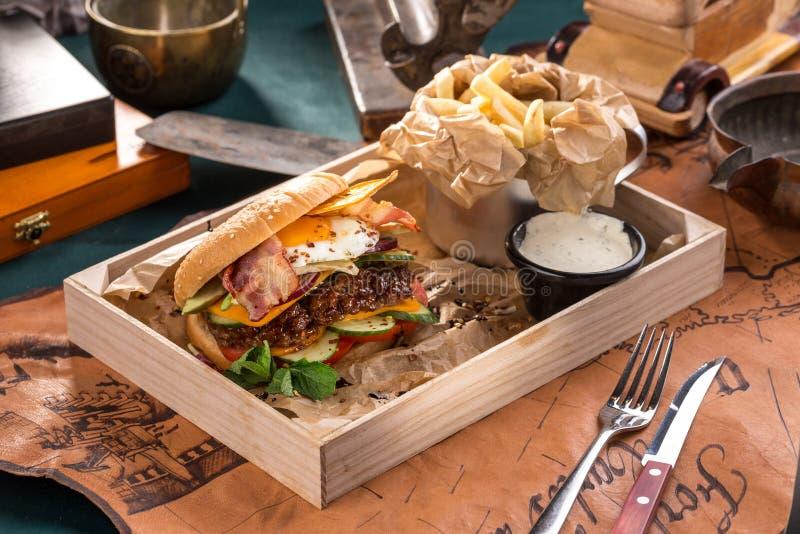 汉堡用在木箱的荷包蛋莴苣蕃茄乳酪红洋葱在老地图背景 库存照片