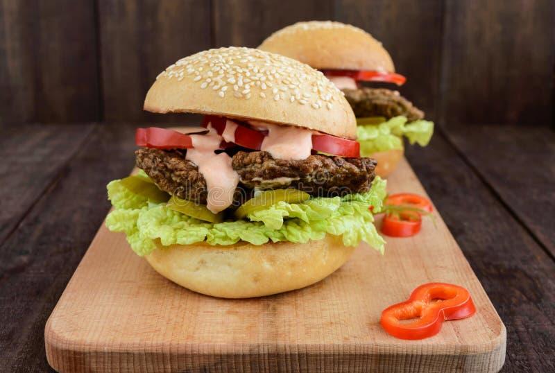 汉堡用肝脏炸肉排、蕃茄、腌汁、莴苣、辣调味汁和一个软的小圆面包与芝麻籽在切板 免版税库存照片