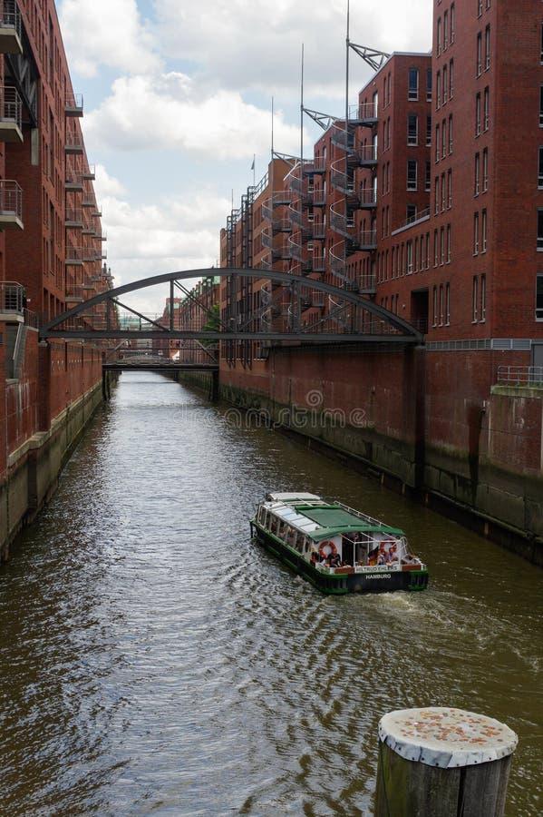 汉堡,德国- 2015年7月18日:运送在历史的Speicherstadt房子和桥梁运河晚上与 库存图片