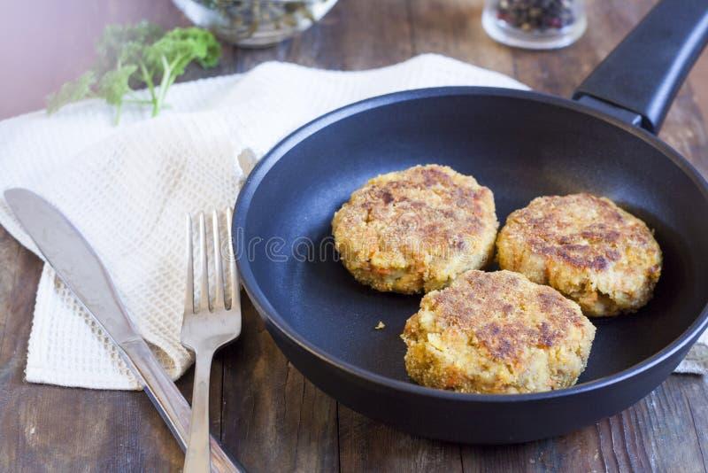 汉堡(炸肉排)在煎锅 汉堡(炸肉排)在木桌上的煎锅 库存照片