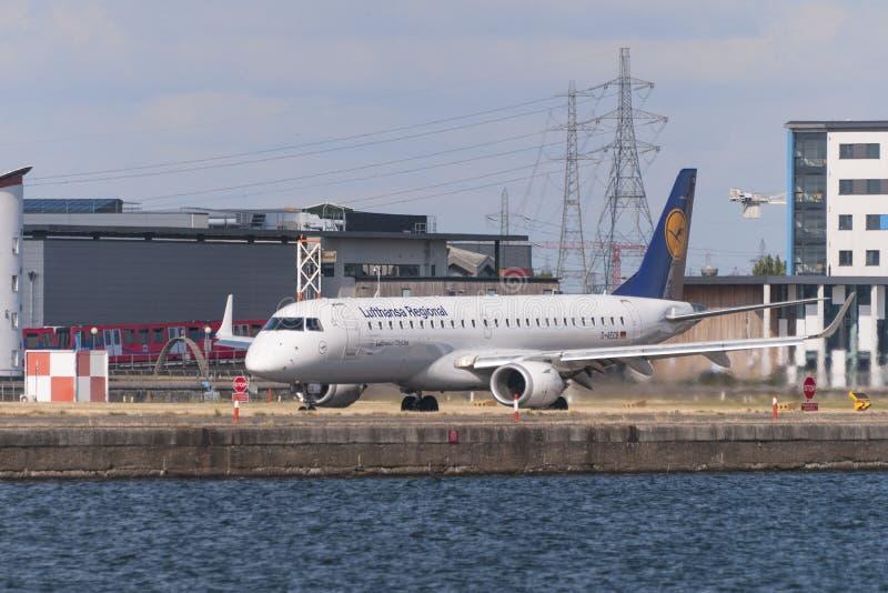 汉莎航空公司在准备好汉莎区域航空的号衣的巴西航空工业公司ERJ-190LR离开在跑道 图库摄影