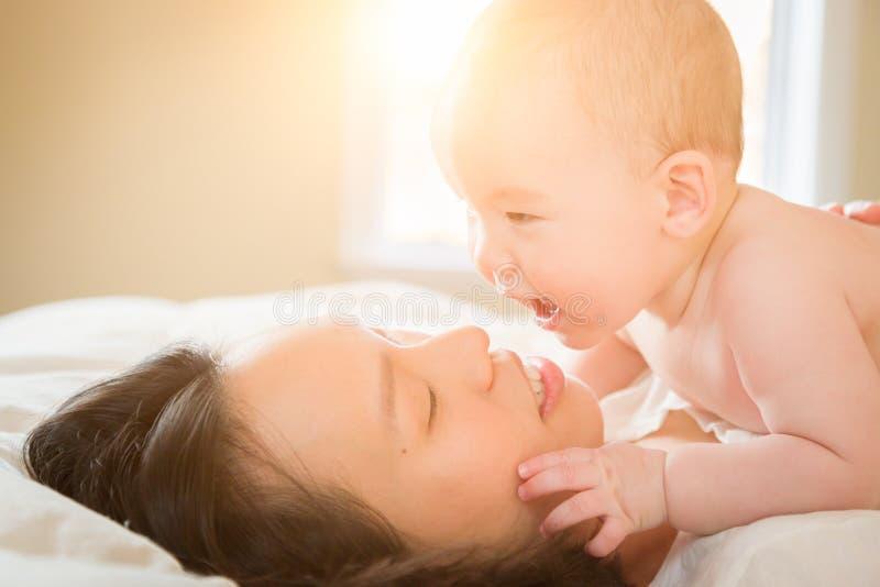 汉语的混合的族种和放置在与他的床上的白种人男婴 库存图片
