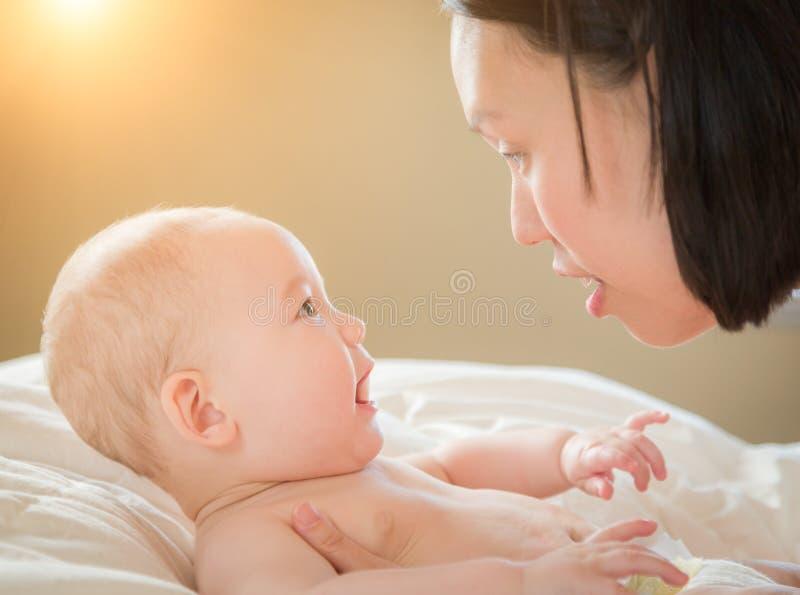 汉语的混合的族种和放置在与他的床上的白种人男婴 免版税库存图片
