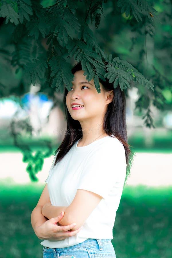 汉语美丽的年轻亚裔的妇女将喜欢放松在绿色自然背景画象垂直 库存图片