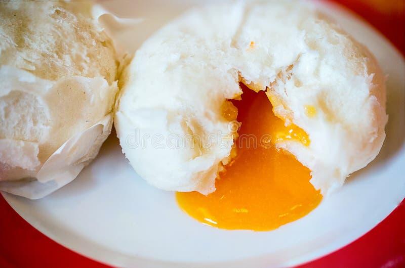 汉语蒸了小圆面包和橙色甜乳脂状的熔岩在中国样式盘 库存照片