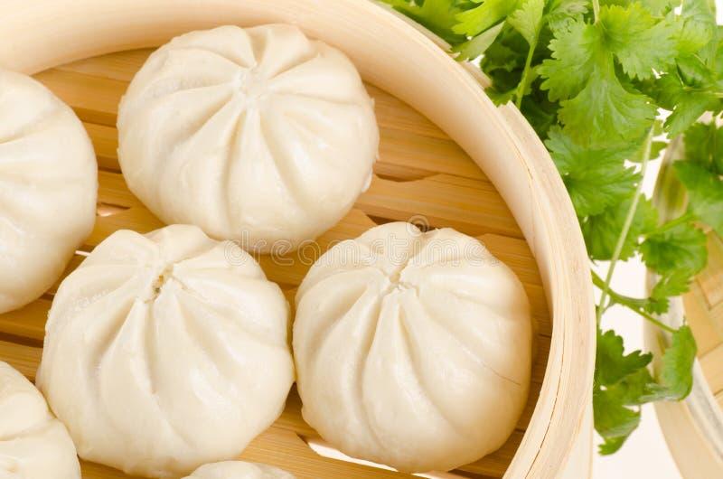 汉语蒸在竹火轮篮子的小圆面包与在w的香菜 库存照片