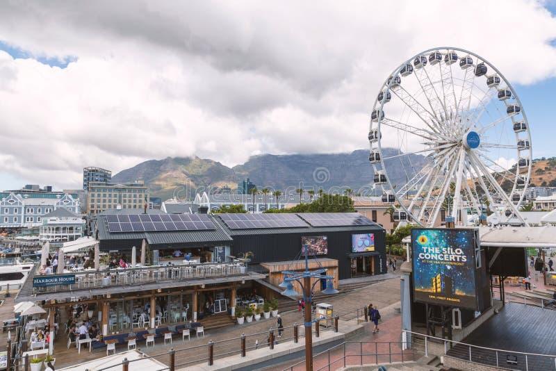 江边地方看法有商店的,餐馆和弗累斯大转轮和桌山视图 库存照片