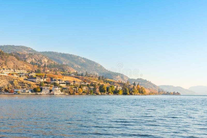 江边家和山在湖有蓝天和温暖的光的从晚上阳光在秋天 库存图片