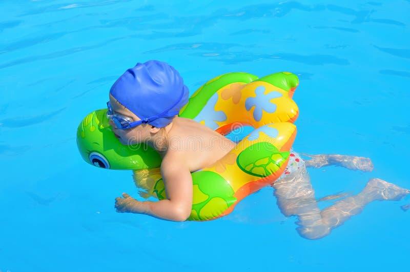 水池佩带的游泳的一个孩子与橡胶环 免版税图库摄影
