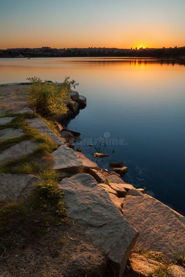 池塘的岸有城市地平线的在日落 库存图片