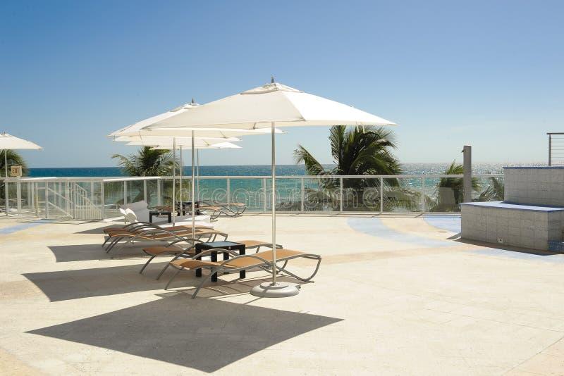 水池旁边伞和椅子 免版税图库摄影